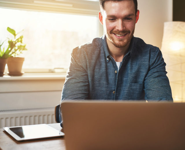 Man smiling at laptop