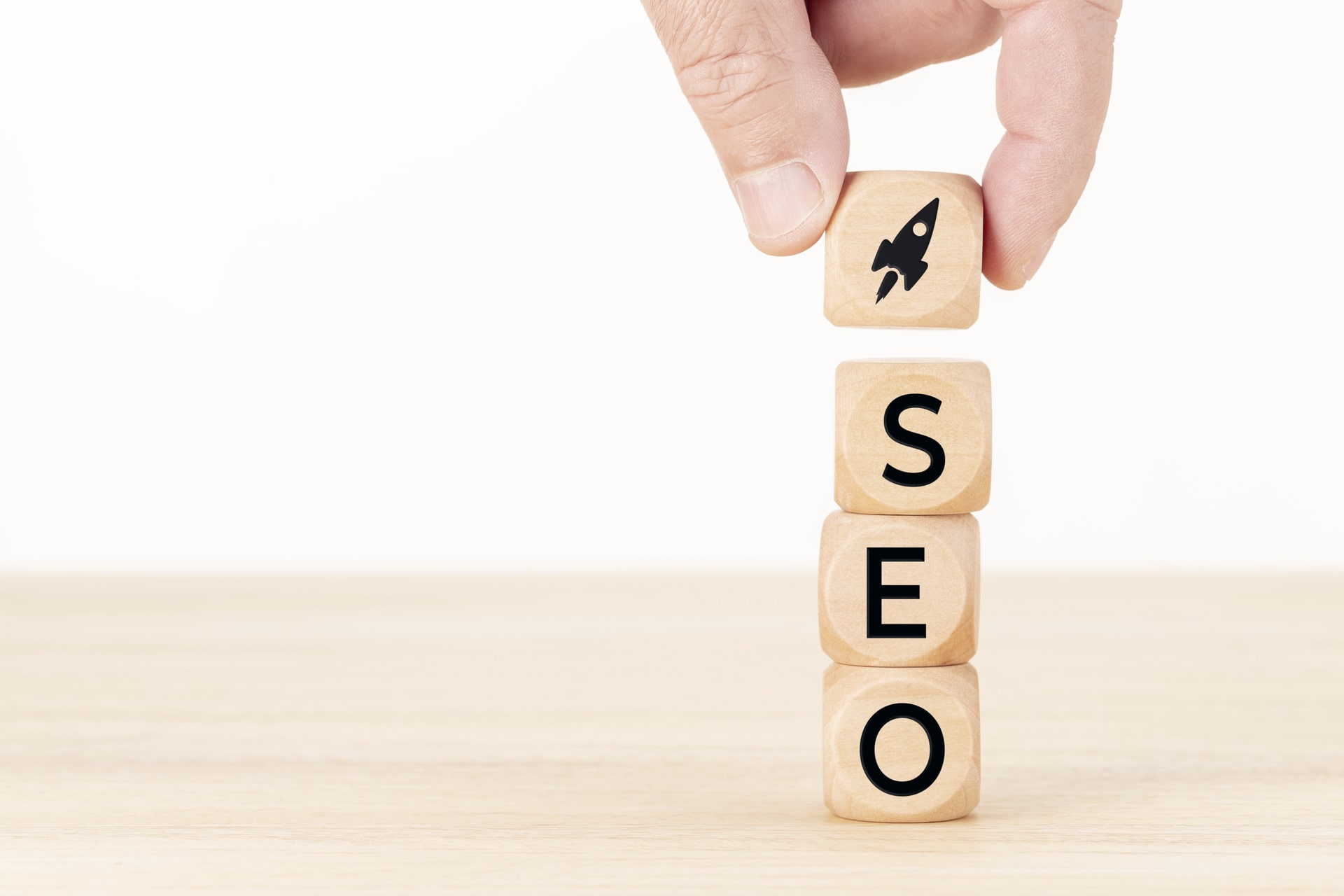Human Hand Holding a Wooden block with Rocket Icon and SEO Word.